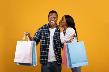 Seasonal sale and great offer. Surprised young african american guy with open mouth shows many color packages, lady kissing him on cheek, isolated on yellow background, studio shot, copy space