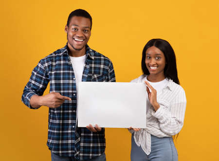 Sale and great offer from couple. Cheerful young african american male and female holding banner with blank space, guy shows with finger at poster, isolated on yellow background, studio shot