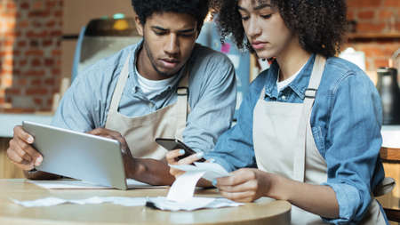 Concentrated professional administrative managers of coffee shop make revisions after working day using tablet. Sad millennial african american couple calculating finance and have problems, panorama Foto de archivo