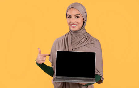 Great Website. Muslim Lady Pointing At Laptop Computer Empty Screen Recommending Internet Service Or Blog Standing Posing On Yellow Studio Background. Mockup Фото со стока