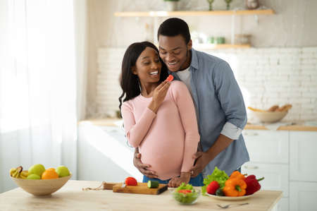 Lovely black pregnant woman feeding her husband with vegetables while cooking in kitchen. Happy romantic expectant couple making lunch together, spending cozy family moments at home