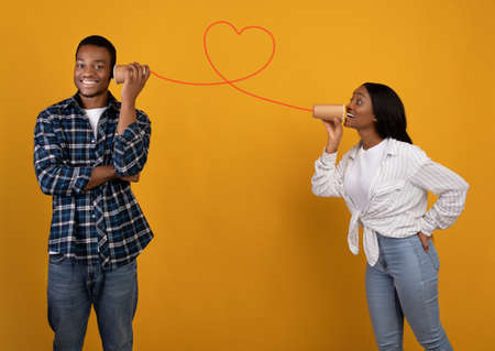 Have fun together and bond of couple in love. Smiling african american woman speaks into paper cup, man listening, through heart shaped red thread, isolated on yellow background, studio shot