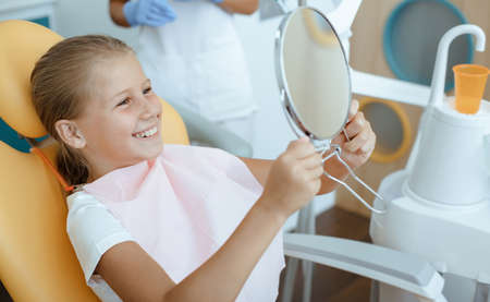 Healthy teeth, good result of work and perfect smile after treatment. Small child looks at mirror after caries procedure, sits at dentist chair in modern clinic interior with equipment 版權商用圖片