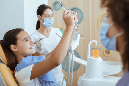 Successful tooth cure procedure and pediatric dental clinic, modern office for children. Happy small kid look at mirror, near dentist and nurse in coats, protective masks and rubber gloves, cropped 版權商用圖片