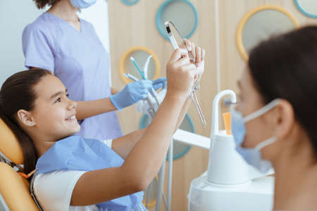 Satisfied dentist clinic patient look at her perfect smile in mirror after treatment in office with medical equipment in background and nurse in white coat, protective mask and rubber gloves, cropped