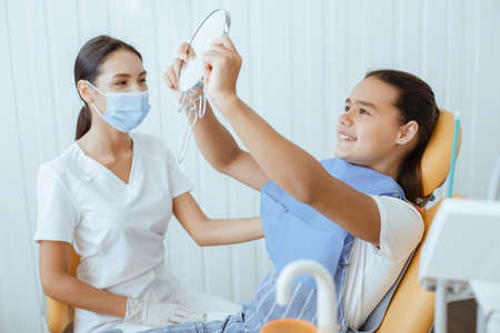 Reception, examination of patient and teeth care. Little hispanic girl smile, look in mirror after dental treatment at dentist in white coat, protective mask and gloves in modern clinic, free space