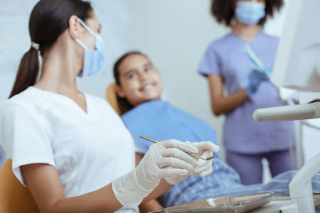 Girl visiting dentist for routine examination. Young lady doctor in uniform, rubber gloves and mask with tool treats tooth of smiling little child in chair with help of african american nurse