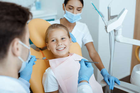 Modern dental examination and oral cavity treatment in children. Cheerful little kid in medical chair looks at millennial male doctor in white coat, protective mask and rubber gloves works with team