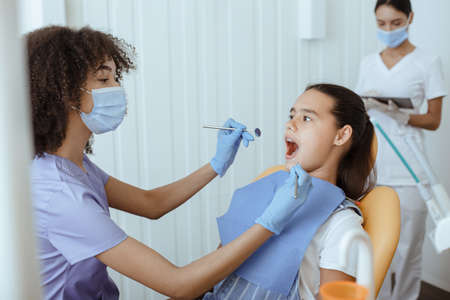 Dental procedure, drilling, tooth extraction. Millennial african american lady doctor in uniform, protective mask and gloves with tool, treat oral cavity of small hispanic kid in modern clinic