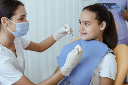Prevention of dental caries and routine medical examination. Young woman dentist in white uniform with protective mask and gloves holds tools and ready to treat teeth of little girl in chair