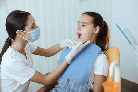 Dentist orthodontics view oral hygiene. Young male doctor in white uniform, protective mask and rubber gloves examines teeth of little girl in medical chair in modern clinic interior, copy space