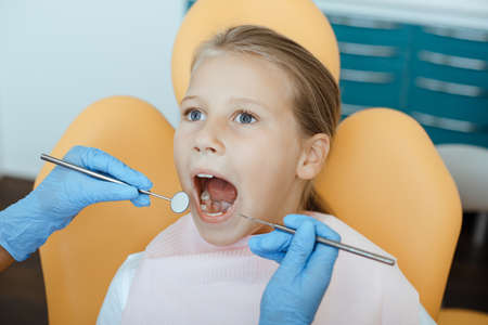 Routine examination of oral cavity. Little girl in medical chair opens her mouth, dentist in rubber gloves with tools treats teeth or put filling, in interior of modern office, close up, copy space 版權商用圖片