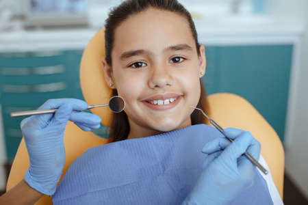 Healthy teeth and medicine concept. Little girl being treatment by dentist at dental clinic, hands of doctor in rubber gloves holding medical instruments near patient mouth, pov, close up, cropped