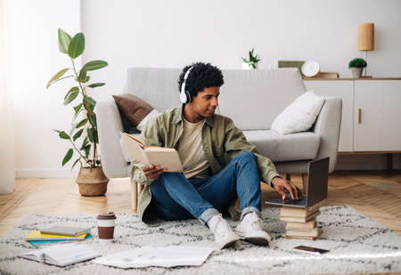 Full length portrait of teen student in headphones taking part in online lesson on laptop, making task from textbook. Black teenager participating in web conference or talking to private tutor