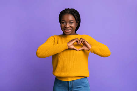 Romantic black lady shaping hands like heart, making love gesture near chest, affectionate african woman expressing kindness, smiling at camera, standing over purple studio background , copy space