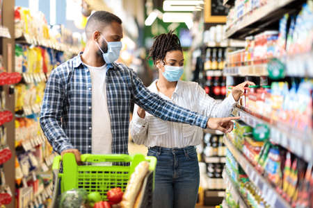 African Husband And Wife In Protective Face Masks Shopping Groceries In Supermarket Buying Food Essentials Walking With Shop Trolley Cart In Grocery Store Indoor. Family Preparing For Quarantine