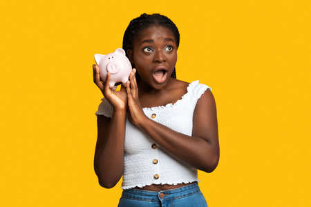 Shocked african american woman listening sound of coins in piggy bank, checking saved money, planning budget for future, emotional black lady standing over yellow studio background with copy space Stockfoto