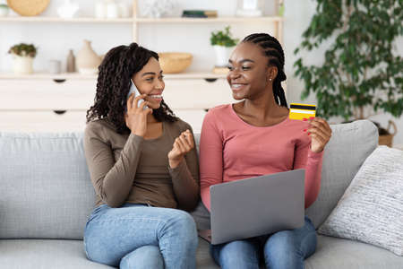 Black cheerful girlfriends ordering food online, making confirmation on smartphone, holding laptop and credit card, empty space. Happy african american women making online order