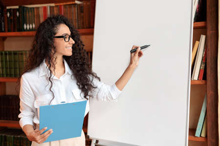 Presentation Concept. Portrait of smiling professional female manager in eyeglasses posing near blank empty whiteboard. Woman in white shirt standing with marker and writing on flipchart, copy space