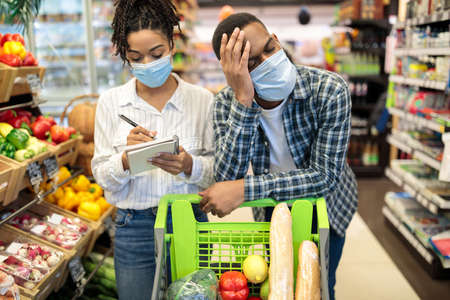 Black Family In Supermarket Buying Food, African Husband Tired Of Grocery Shopping With Wife Standing Near Cart Full Of Food In Groceries Store Indoor. Shop Customers and Consumerism Concept
