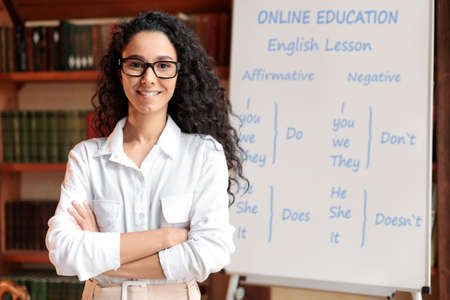 Online Education And E-Learning Concept. Portrait of smiling female teacher standing at whiteboard with English grammar rules. Confident woman in glasses looking at camera, posing with folded arms Stockfoto