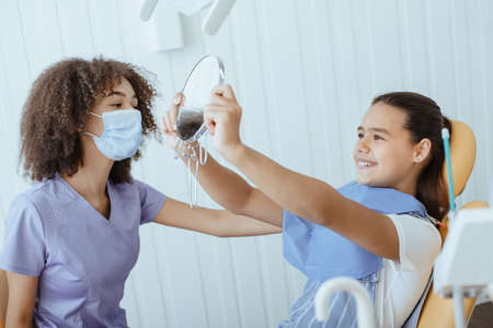 Good procedure and snow-white smile. Happy small girl looks in mirror for estimating dentist work and enjoying result with young african american specialist in uniform, protective mask and gloves Foto de archivo