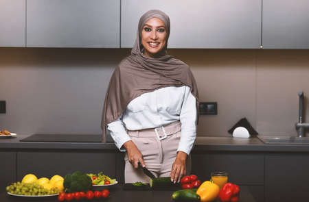 Happy Muslim Lady Cooking In Kitchen, Cutting Fresh Vegetables Making Salad For Dinner At Home, Wearing Hijab. Arab Wife Preparing Healthy Meal Smiling To Camera Indoors. Arabic Cuisine And Recipes