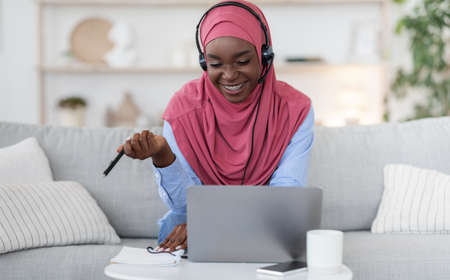 Young African Muslim Woman In Hijab Studying At Home With Online Tutor, Using Laptop Computer And Headset, Talking At Camera, Black Islamic Lady In Hijab Enjoying Distance Learning, Free Space