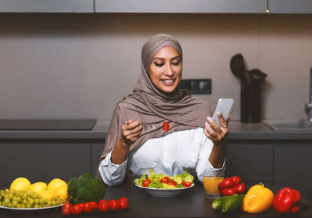 Happy Muslim Woman Using Smartphone Eating Vegetable Salad Having Lunch Sitting In Kitchen At Home. Dieting Mobile Application, Healthy Nutrition And Food, Weight Loss Recipes App For Phone