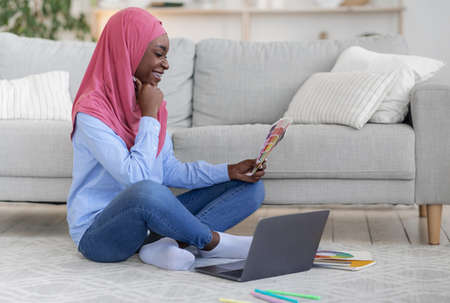 Black Muslim Female Designer Working Remotely At Home With Laptop, Holding Color Samples, African Lady In Hijab Looking At Swatches For New Interior Design, Sitting On Floor In Living Room, Copy Space