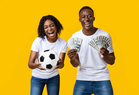 Sport bet excitement, gambing and family lifestyle concept. Excited african-american young couple enjoying their win, standing with soccer ball and lots of money, yellow studio background
