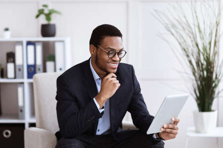 Cheerful black businessman holding digital tablet, office interior, empty space. Smiling african american young entrepreneur using digital pad while working in his office, surfing on internet 版權商用圖片