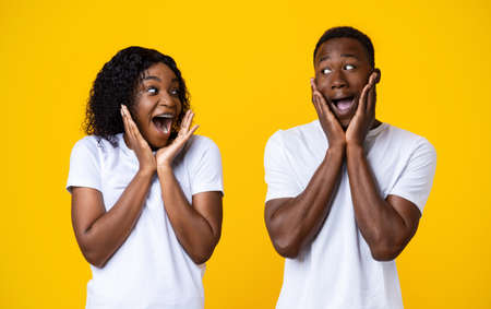 Surprised black couple screaming and looking at each other, expressing emotions, amazement and happiness. African american emotional man and woman got shocking news over yellow studio background