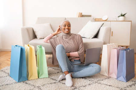 Happy black lady in hijab sitting on floor with laptop and paper bags, shopping on internet at home. Positive Muslim woman purchasing goods online in web store, full length portrait