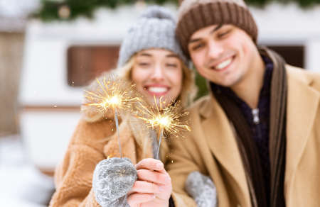 Festive Mood. Cheerful Young Couple Posing With Sparklers Outdoors At Winter Day, Celebrating Christmas Holidays Together, Having Fun At Camping, Standing Near Motorhome Campervan, Selective Focus