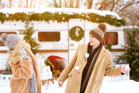 Snow Fight. Joyful millennial couple having fun at winter day, throwing snowballs at each other, spending christmas holidays together at campsite, enjoying traveling with caravan motorhome, free space
