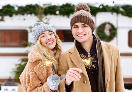 Beautiful Young Couple With Sparklers In Hands Posing At Winter Day Outdoors, Enjoying Spending Christmas Holidays Together, Two Lovers Standing At Campsite Near Modern Campervan, Free Space