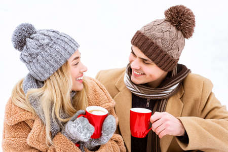 Romantic Young Couple In Winter Clothes Enjoying Hot Chocolate With Marshmallow Outdoors, Affectionate Man And Woman Holding Red Cups And Smiling To Each Other, Closeup Shot, Free Space