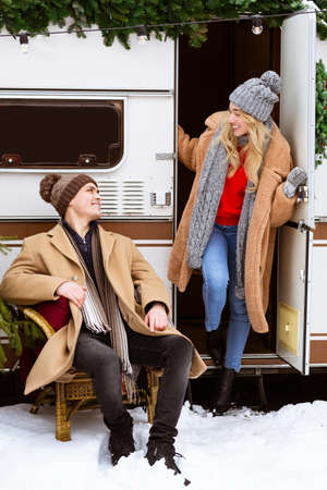 Young romantic couple enjoying traveling with campervan, spending winter day outside, having fun at campsite, loving man and woman celebrating christmas holidays together outdoors, free space