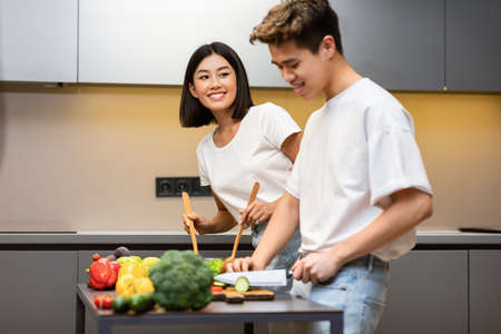 Happy Korean Family Couple Cooking Healthy Food Making Veggie Salad For Dinner Standing In Modern Kitchen At Home. Spouses Cook Meal Together. Selective Focus