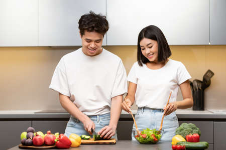 Healthy Recipes. Happy Chinese Spouses Cooking Together Cutting Vegetables For Salad Standing In Kitchen At Home. Asian Family Preparing Dinner On Weekend. Meal Preparation Concept
