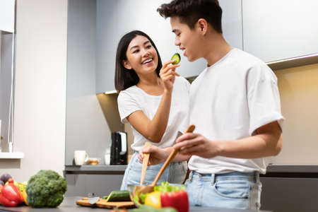Cheerful Japanese Family Couple Tasting Food While Cooking Dinner Together In Modern Kitchen At Home. Meal Preparation Fun, Nutrition And Food Recipes Concept. Selective Focus