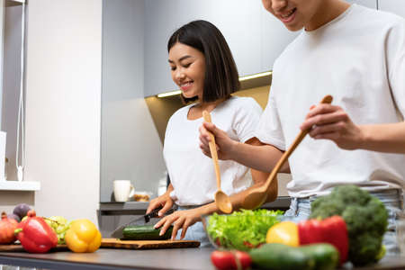 Happy Chinese Family Couple Cooking Salad Together Preparing Tasty Dinner Together In Kitchen, Asian Husband Helping Wife Cook Meal At Home. Food Preparation. Selective Focus, Cropped 免版税图像