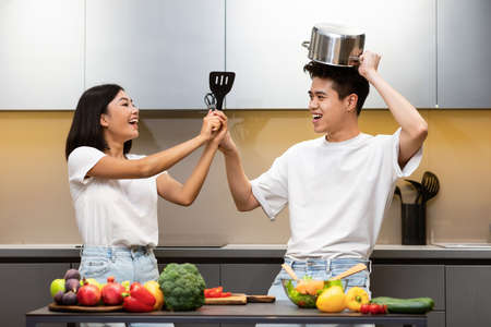Happy Japanese Family Fencing With Cooking Tools Having Fun In Modern Kitchen At Home. Carefree Couple Preparing Dinner And Laughing Together, Enjoying Meal Preparation