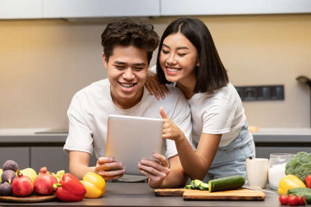 Asian Boyfriend And Girlfriend Cooking With Digital Tablet In Modern Kitchen At Home, Searching Dinner Recipe Online Preparing Meal Together. Cooking App, Food Recipes Website Concept