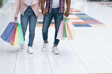 Consumerism Concept. Unrecognizable Black Couple Walking With Colorful Shopping Bags In Mall, Holding Hands While Doing Purchases Together In Department Store, Cropped Image With Copy Space