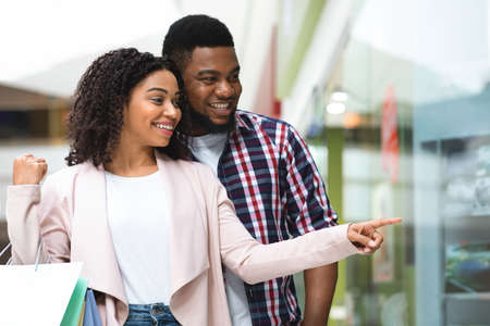 Lets Buy This. Happy Black Woman Shopping With Boyfriend In Mall, Pointing With Finger At Showcase In Department Store, Young African American Couple Enjoying Seasonal Sales And Discounts, Copy Space