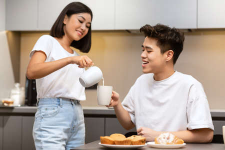 Chinese Wife Adding Milk To Husbands Coffee During Family Breakfast On Weekend Morning In Kitchen At Home. Cheerful Asian Housewife Caring For Her Spouse Eating Together. 免版税图像
