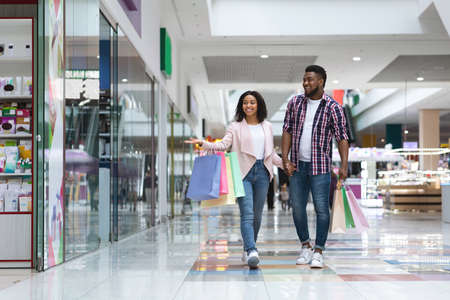 Happy African American Couple Doing Shopping In Mall Together, Enjoying Seasonal Sales And Discounts, Cheerful Black Spouses Looking At Showcases While Walking With Shopper Bags In Department Store
