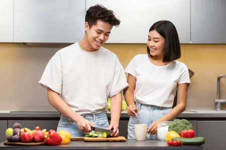 Healthy Dinner Recipe. Chinese Husband And Wife Cooking Vegetable Salad In Modern Kitchen, Cutting Fresh Veggies Preparing Meal Together At Home. Food Preparation And Family Nutrition Concept